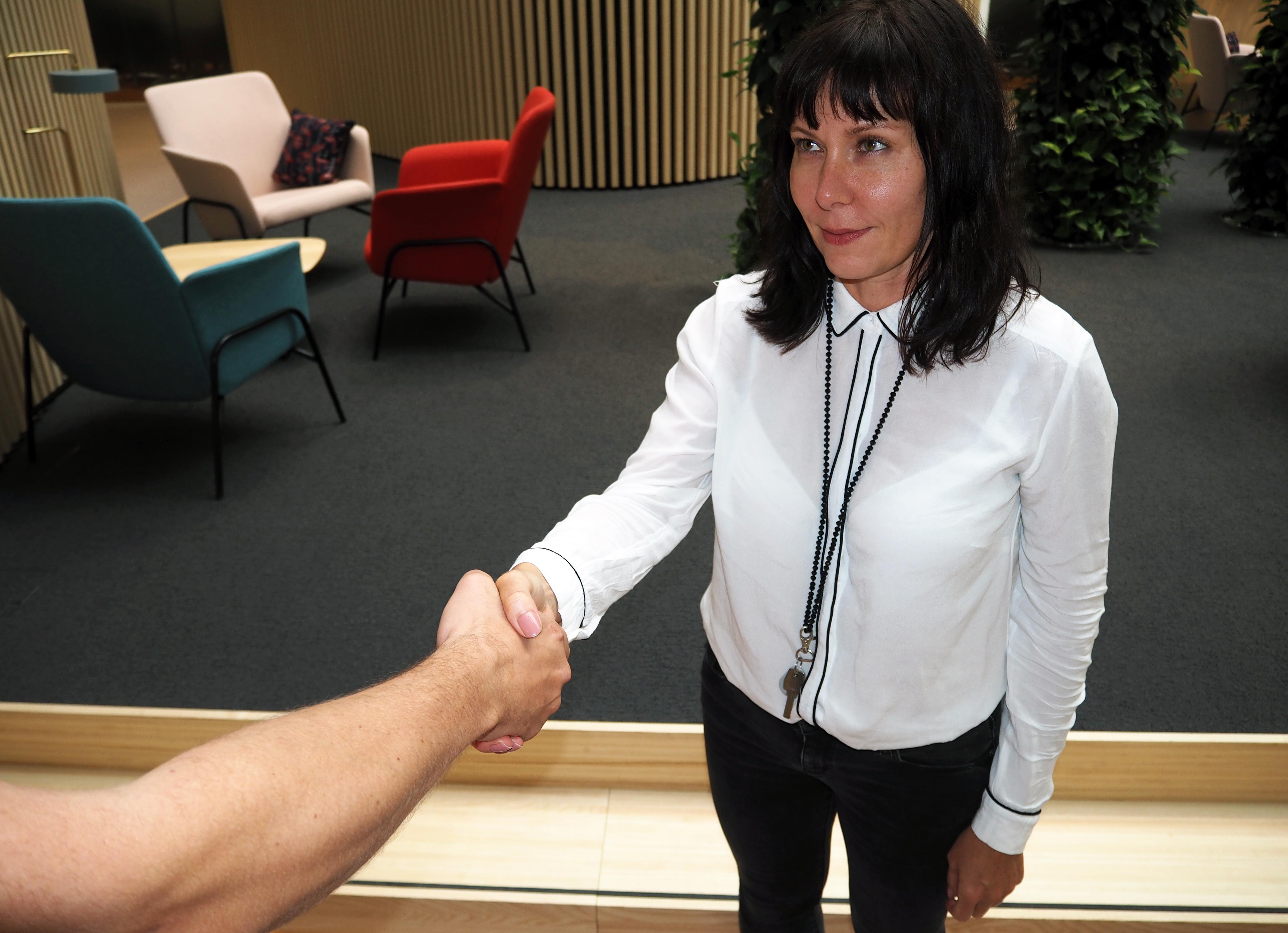 Omenan toimitusjohtaja Kati Niemelä kättelemässä yhteityökumppania.