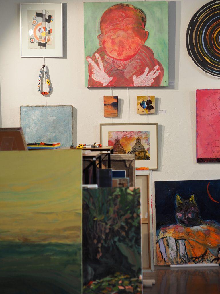 Värikkäät maalaukset on ripustettu seinälle