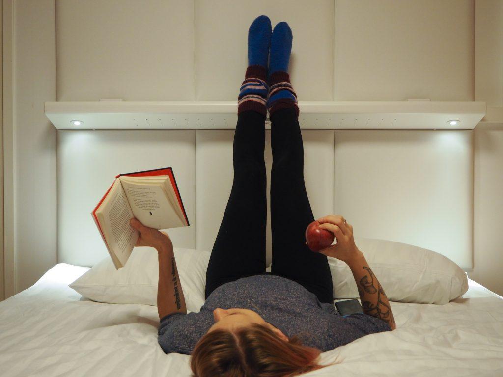 Jalkojen rentouttaista ja lukemista Omena-hotellin huoneessa
