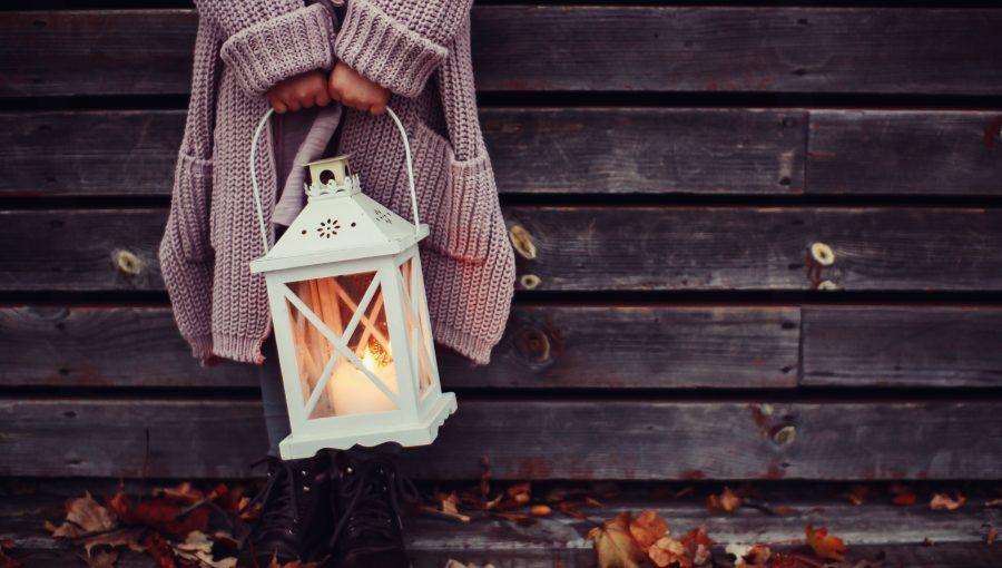 Nainen seisoo lyhty kädessään syksyllä