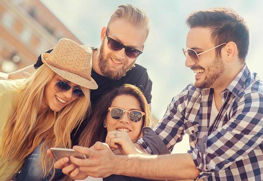 Ryhmä nuoria aikuisia nauttimassa aurinkoisesta kaupungista.