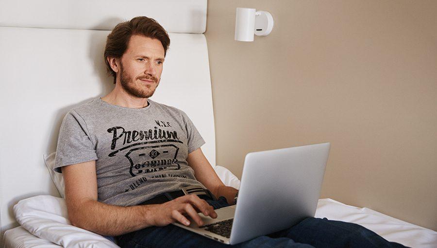 Mies istuu sängyllä läppäri sylissään Lönnrotin kadun Omena-hotellin uudessa Single-huoneessa.