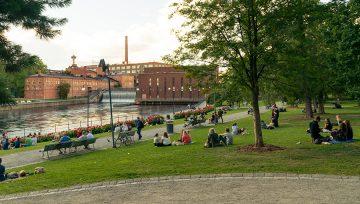 Ihmisiä nauttimassa kesäillasta Tampereen Koskipuistossa