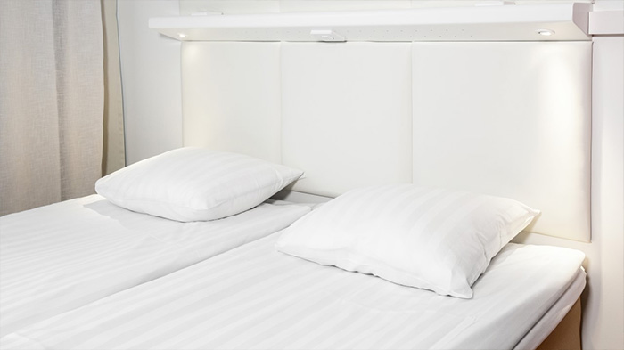 Omena-hotellin uudistuneen huoneilmeen mukainen sängynpääty