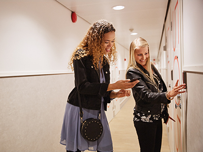 Tytöt näppäilevät ovikoodia Lönnrotinkadun Omena-hotellin käytävällä.