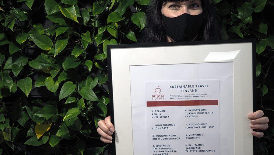 Omenan toimitusjohtaja Kati Niemelä poseeraa viherseinän edessä pidellen taulua, jossa on listattu 10 kestävän matkalun periaatetta.